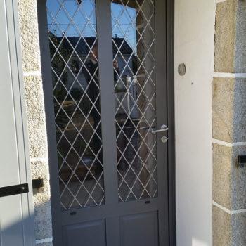 porte d'entrée aluminium noire avec vitres et grillage