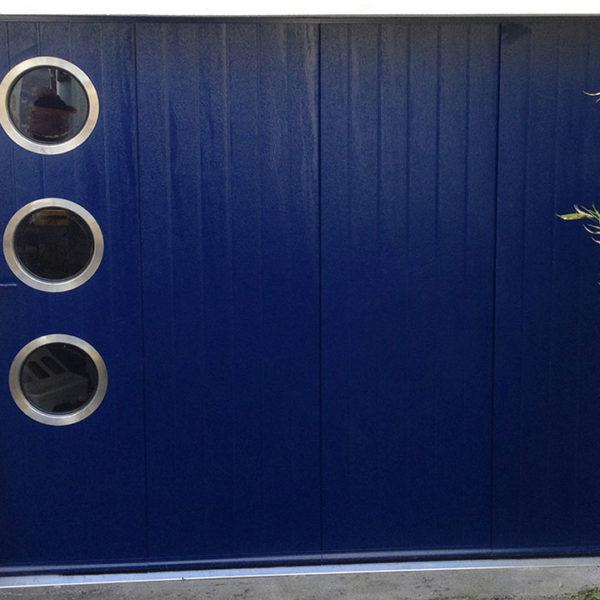 porte de garage latérale bleue avec 3 hublots